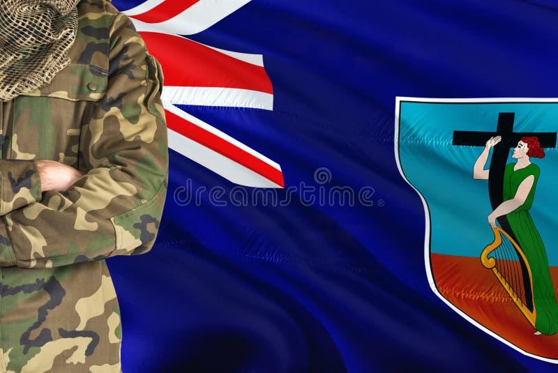有全国挥动的旗子的横渡的胳膊战士在背景-蒙特塞拉特军事题材 图库摄影