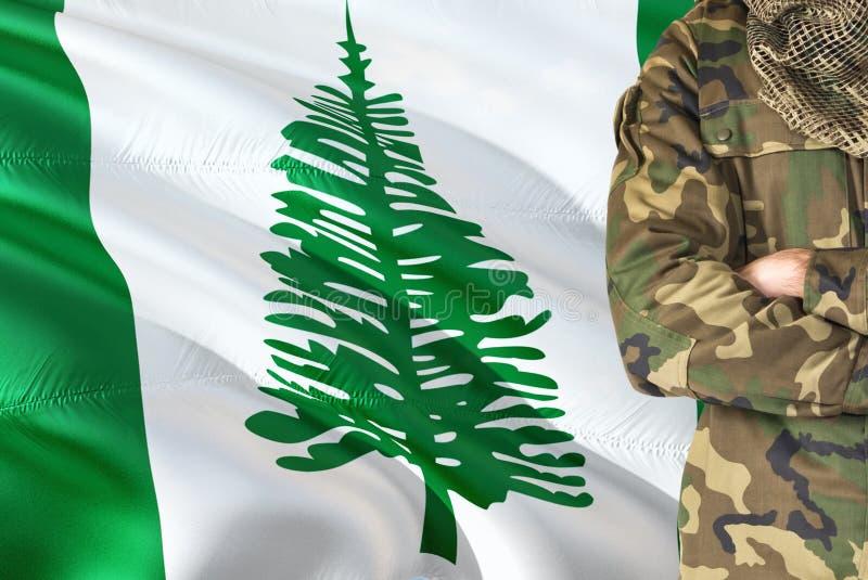 有全国挥动的旗子的横渡的胳膊战士在背景-诺福克岛军事题材 免版税库存照片