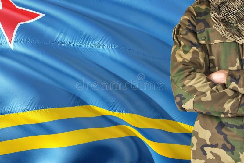 有全国挥动的旗子的横渡的胳膊战士在背景-阿鲁巴军事题材 免版税图库摄影