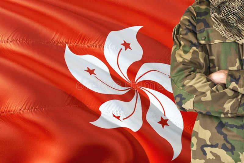 有全国挥动的旗子的横渡的胳膊战士在背景-香港军事题材 库存图片
