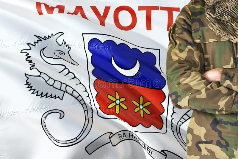 有全国挥动的旗子的横渡的胳膊战士在背景-马约特军事题材 图库摄影