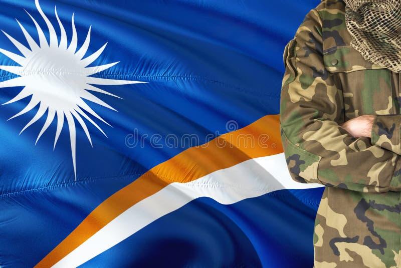 有全国挥动的旗子的横渡的胳膊战士在背景-马绍尔群岛军事题材 免版税图库摄影