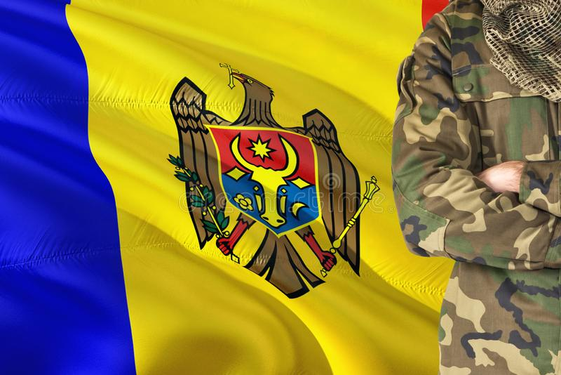 有全国挥动的旗子的横渡的胳膊摩尔多瓦的士兵在背景-摩尔多瓦军事题材 库存图片