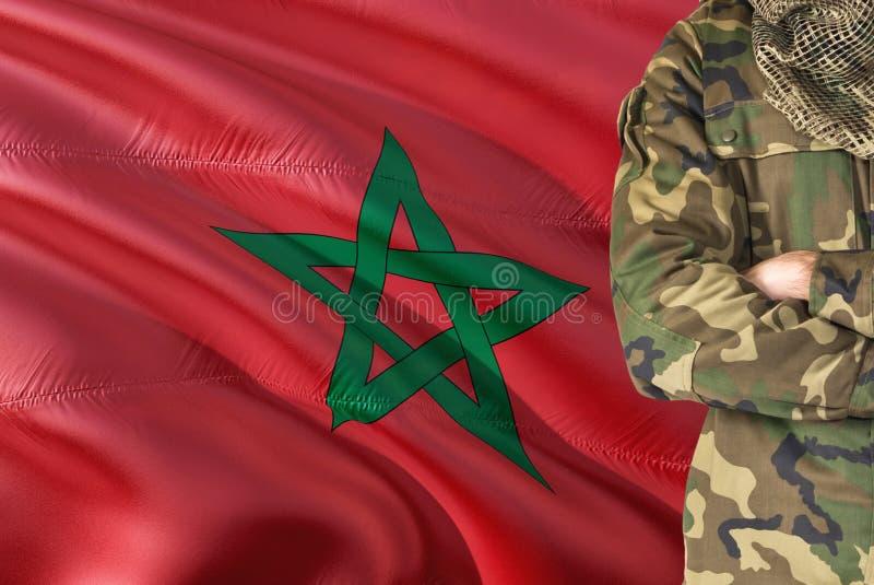 有全国挥动的旗子的横渡的胳膊摩洛哥士兵在背景-摩洛哥军事题材 免版税库存图片