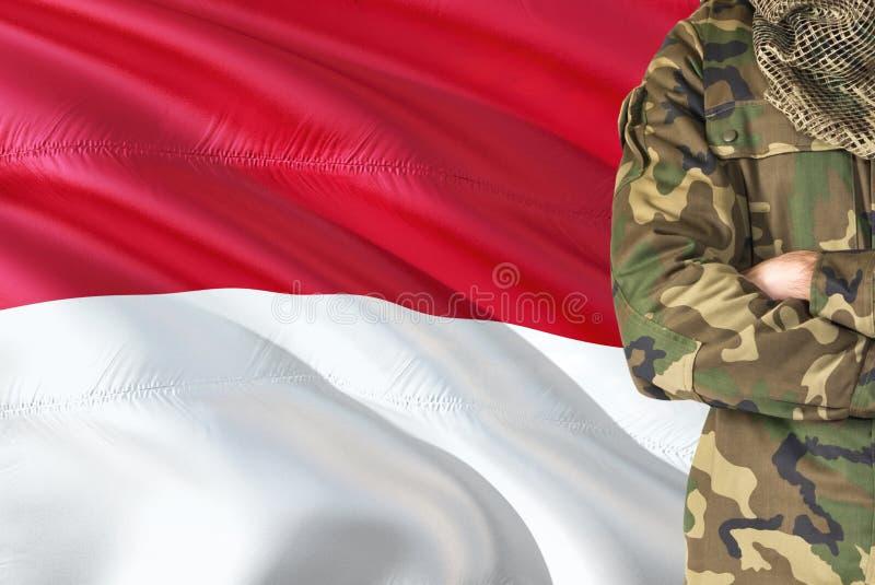 有全国挥动的旗子的横渡的胳膊摩纳哥战士在背景-摩纳哥军事题材 图库摄影