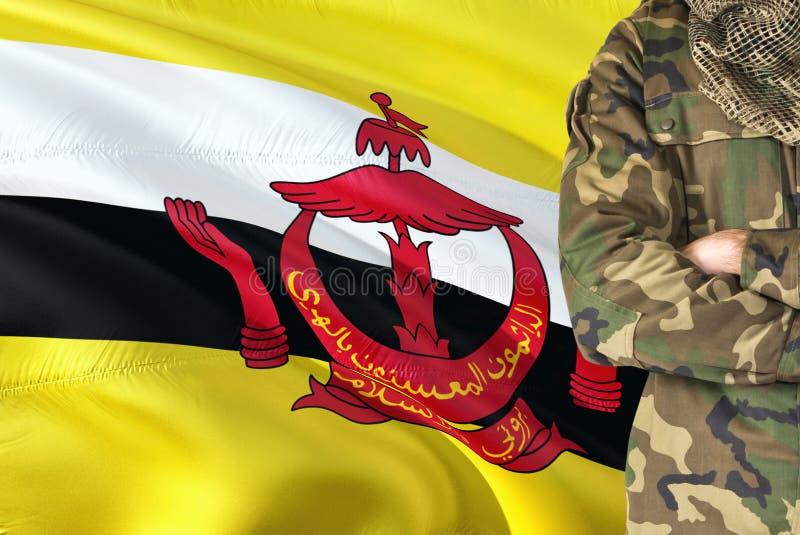 有全国挥动的旗子的横渡的胳膊文莱的战士在背景-文莱军事题材 免版税图库摄影