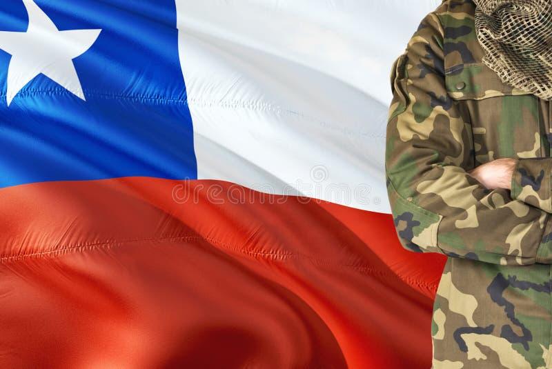 有全国挥动的旗子的横渡的胳膊智利士兵在背景-智利军事题材 免版税库存照片