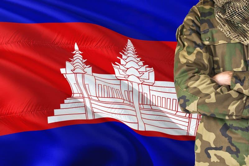 有全国挥动的旗子的横渡的胳膊柬埔寨士兵在背景-柬埔寨军事题材 图库摄影
