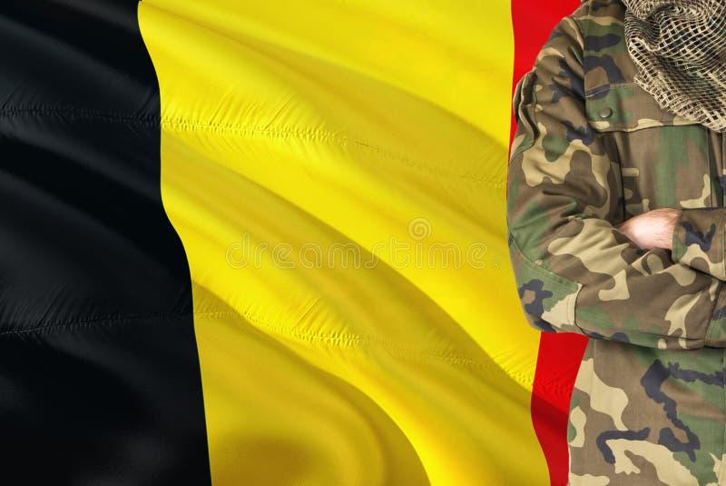 有全国挥动的旗子的横渡的胳膊比利时士兵在背景-比利时军事题材 库存图片