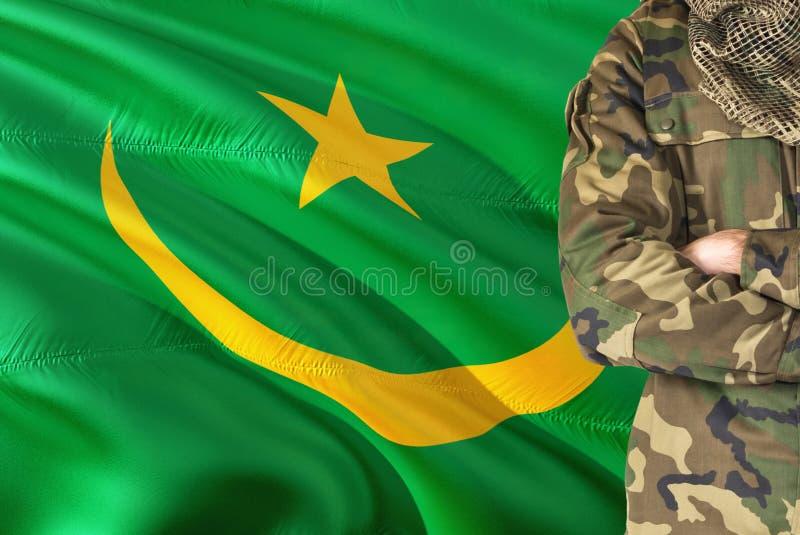 有全国挥动的旗子的横渡的胳膊毛里塔尼亚士兵在背景-毛里塔尼亚军事题材 免版税库存照片