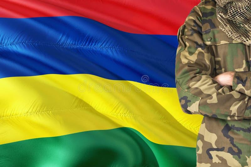 有全国挥动的旗子的横渡的胳膊毛里求斯士兵在背景-毛里求斯军事题材 免版税库存图片
