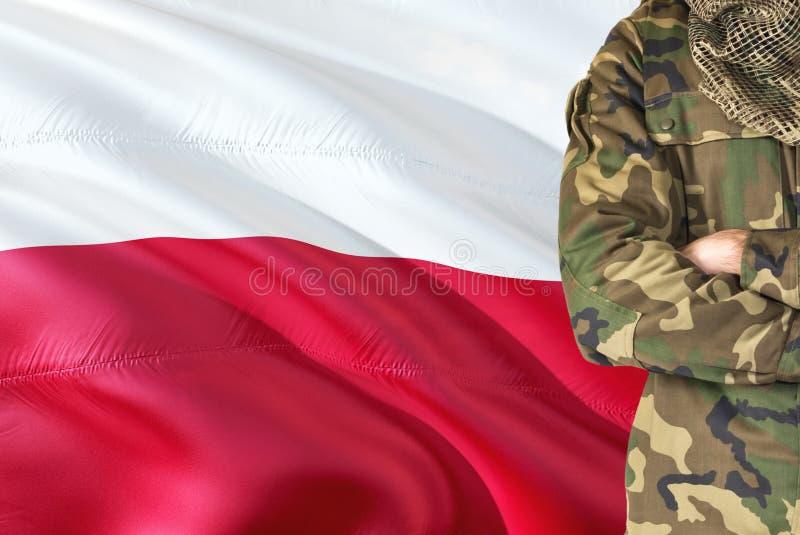 有全国挥动的旗子的横渡的胳膊波兰士兵在背景-波兰军事题材 免版税库存照片
