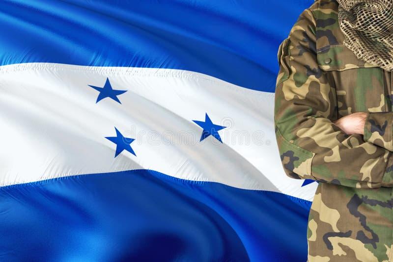 有全国挥动的旗子的横渡的胳膊洪都拉斯战士在背景-洪都拉斯军事题材 免版税库存图片