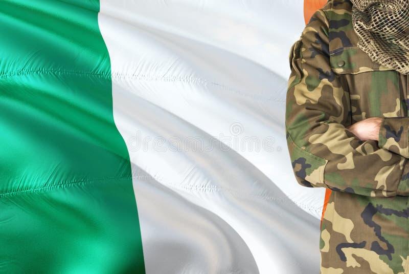 有全国挥动的旗子的横渡的胳膊爱尔兰士兵在背景-爱尔兰军事题材 库存图片
