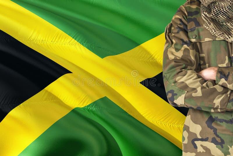 有全国挥动的旗子的横渡的胳膊牙买加士兵在背景-牙买加军事题材 免版税库存图片
