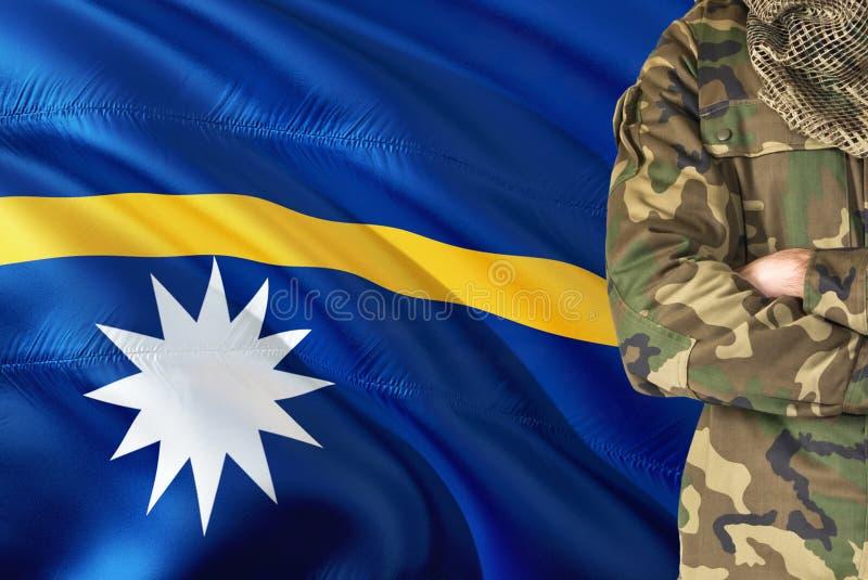 有全国挥动的旗子的横渡的胳膊瑙鲁战士在背景-瑙鲁军事题材 库存照片
