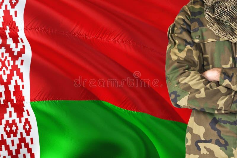 有全国挥动的旗子的横渡的胳膊白俄罗斯语战士在背景-白俄罗斯军事题材 库存图片