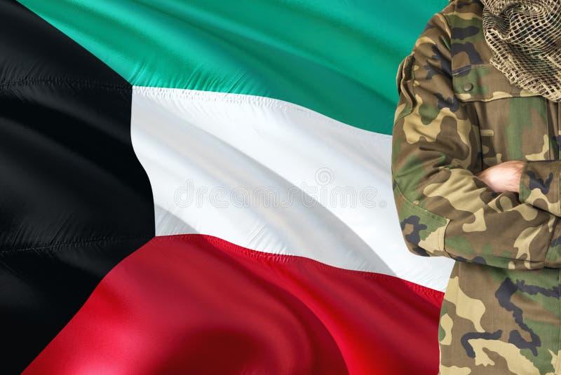 有全国挥动的旗子的横渡的胳膊科威特士兵在背景-科威特军事题材 免版税库存图片