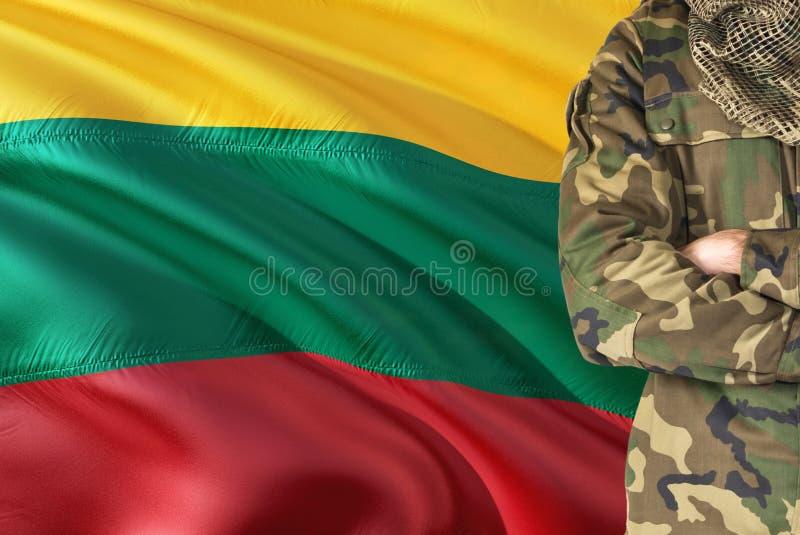 有全国挥动的旗子的横渡的胳膊立陶宛士兵在背景-立陶宛军事题材 免版税库存图片