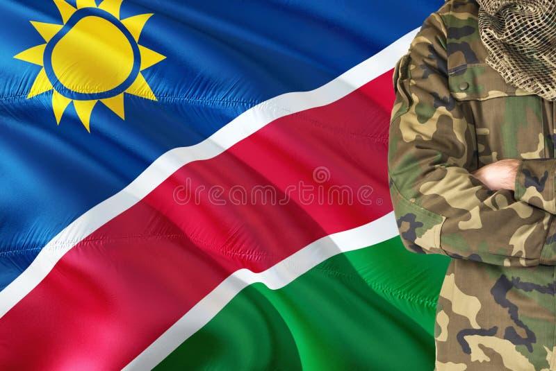 有全国挥动的旗子的横渡的胳膊纳米比亚士兵在背景-纳米比亚军事题材 免版税库存照片