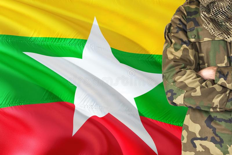 有全国挥动的旗子的横渡的胳膊缅甸士兵在背景-缅甸军事题材 免版税库存照片