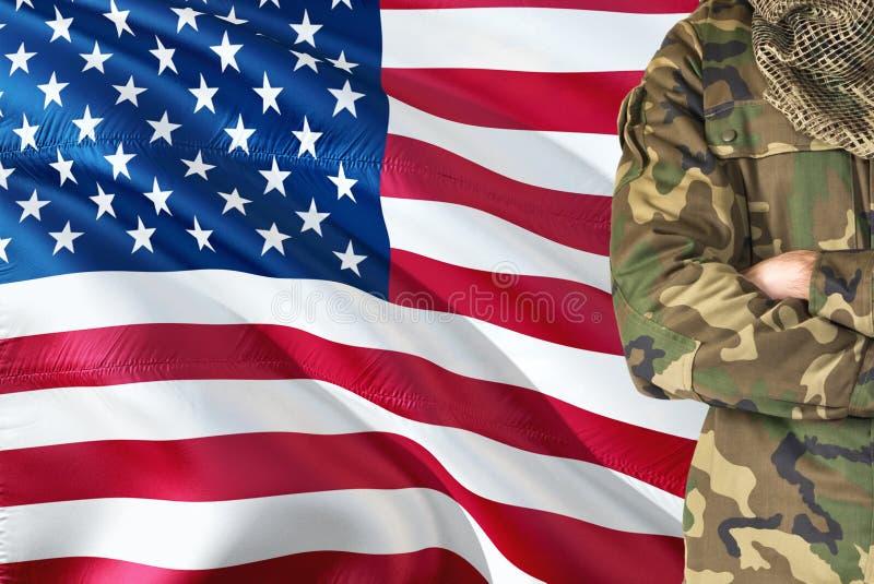 有全国挥动的旗子的横渡的胳膊美军士兵在背景-美国军事题材 库存照片