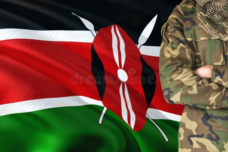 有全国挥动的旗子的横渡的胳膊肯尼亚战士在背景-肯尼亚军事题材 库存图片