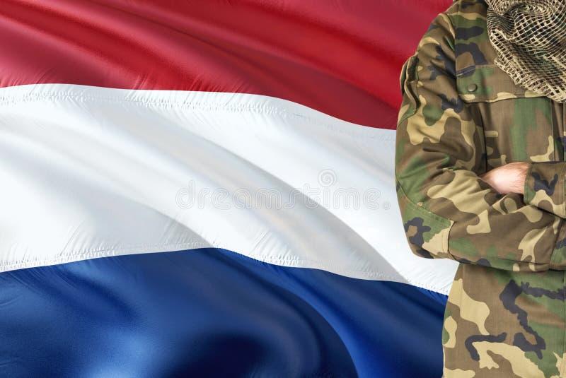 有全国挥动的旗子的横渡的胳膊荷兰士兵在背景-荷兰军事题材 免版税图库摄影