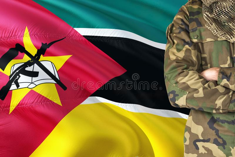 有全国挥动的旗子的横渡的胳膊莫桑比克士兵在背景-莫桑比克军事题材 库存图片