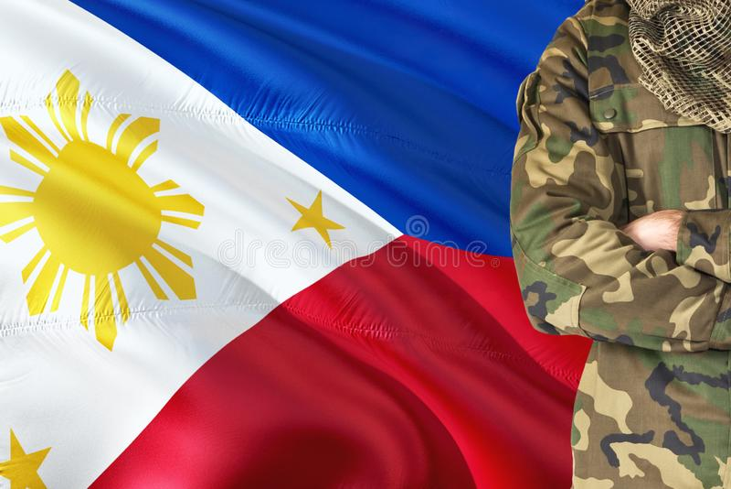 有全国挥动的旗子的横渡的胳膊菲律宾士兵在背景-菲律宾军事题材 免版税库存图片
