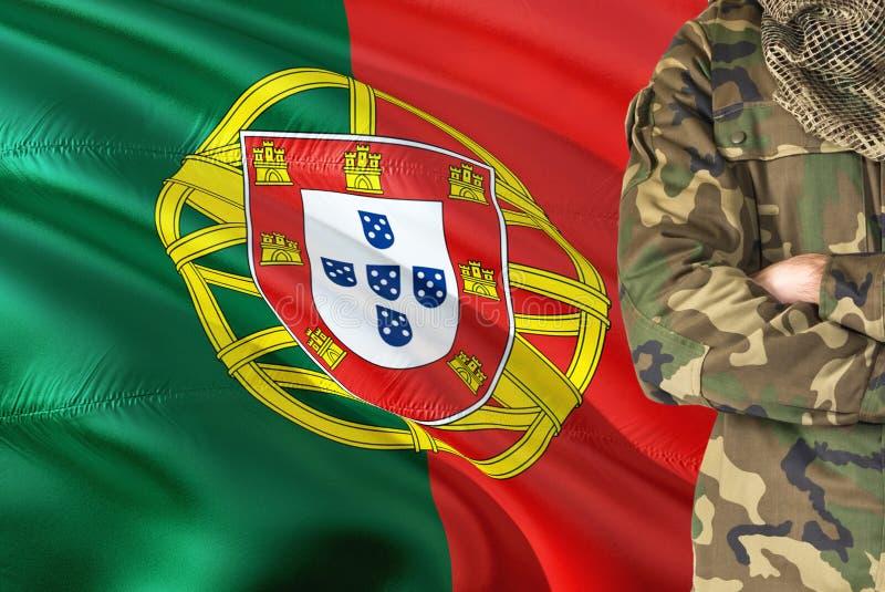 有全国挥动的旗子的横渡的胳膊葡萄牙士兵在背景-葡萄牙军事题材 库存照片