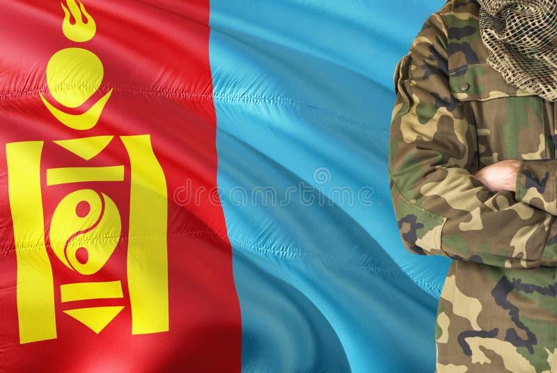 有全国挥动的旗子的横渡的胳膊蒙古战士在背景-蒙古军事题材 库存图片