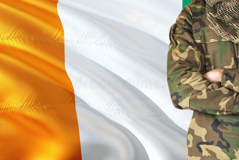有全国挥动的旗子的横渡的胳膊象牙海岸士兵在背景-科特迪瓦军事题材 免版税库存图片