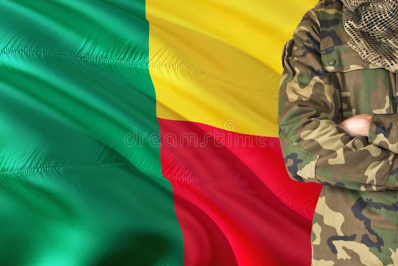 有全国挥动的旗子的横渡的胳膊贝宁的战士在背景-贝宁军事题材 库存照片