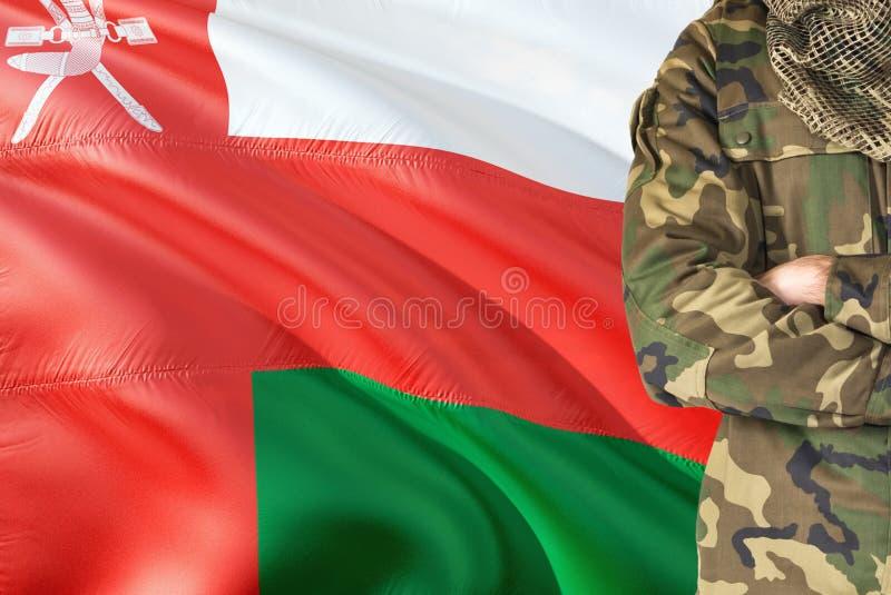 有全国挥动的旗子的横渡的胳膊阿曼士兵在背景-阿曼军事题材 免版税库存照片