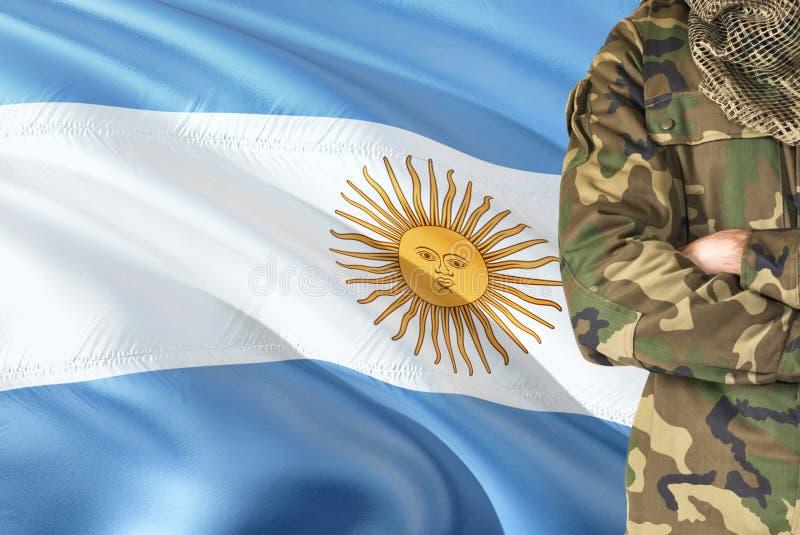 有全国挥动的旗子的横渡的胳膊阿根廷士兵在背景-阿根廷军事题材 库存图片