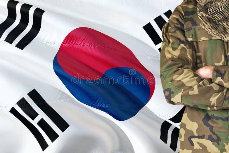 有全国挥动的旗子的横渡的胳膊韩国士兵在背景-韩国军事题材 免版税图库摄影