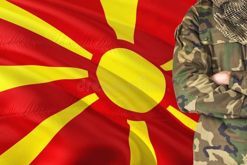有全国挥动的旗子的横渡的胳膊马其顿士兵在背景-马其顿军事题材 免版税图库摄影
