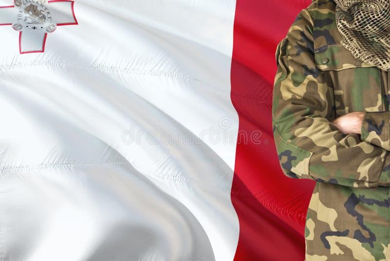 有全国挥动的旗子的横渡的胳膊马尔他战士在背景-马耳他军事题材 库存照片