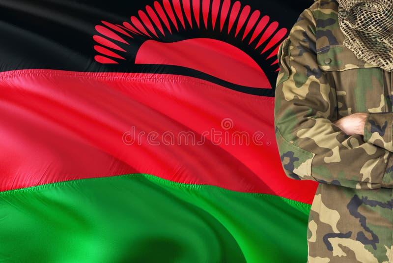 有全国挥动的旗子的横渡的胳膊马拉维士兵在背景-马拉维军事题材 库存照片