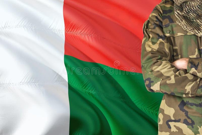 有全国挥动的旗子的横渡的胳膊马达加斯加人的战士在背景-马达加斯加军事题材 免版税图库摄影