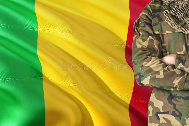 有全国挥动的旗子的横渡的胳膊马里士兵在背景-马里军事题材 库存照片