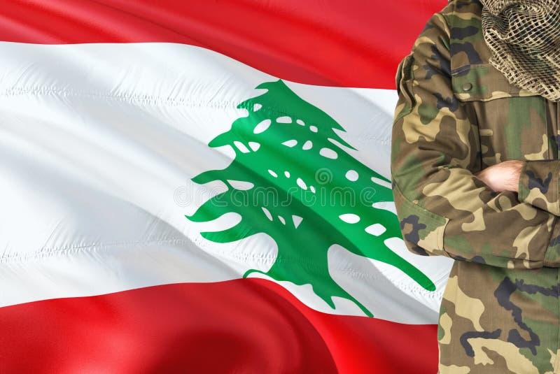 有全国挥动的旗子的横渡的胳膊黎巴嫩士兵在背景-黎巴嫩军事题材 免版税库存照片