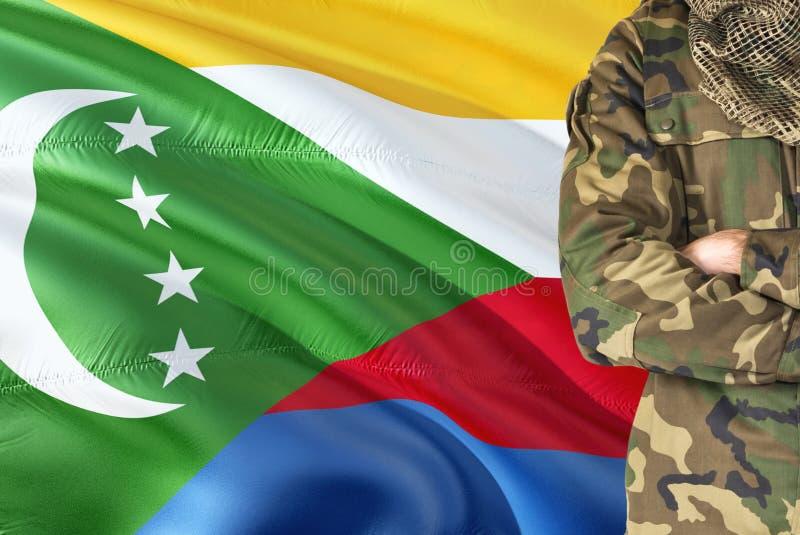 有全国挥动的旗子的横渡的胳膊Comoran战士在背景-科摩罗军事题材 免版税库存图片