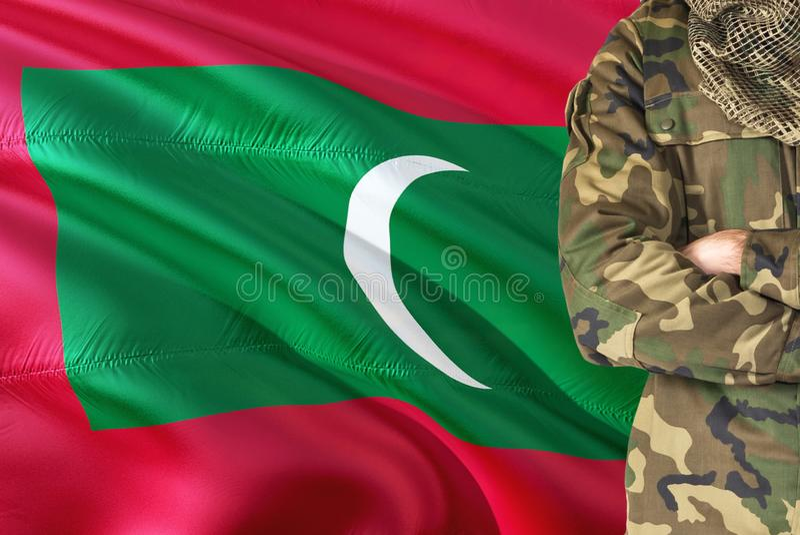 有全国挥动的旗子的横渡的胳膊Maldivan战士在背景-马尔代夫军事题材 库存图片