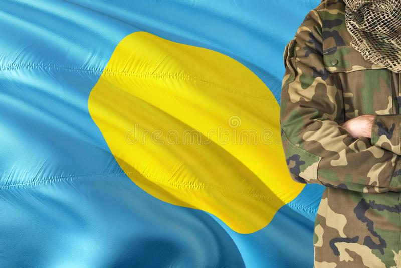 有全国挥动的旗子的横渡的胳膊Palauan战士在背景-帕劳军事题材 免版税图库摄影