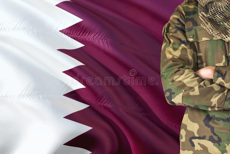 有全国挥动的旗子的横渡的胳膊Qatari战士在背景-卡塔尔军事题材 免版税图库摄影