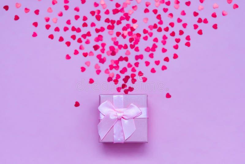 有全息照相的红心的桃红色礼物盒在淡色背景 欢乐的背景 顶视图 免版税库存图片