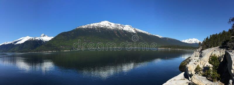 有全景积雪覆盖的山的阿拉斯加原野- 图库摄影