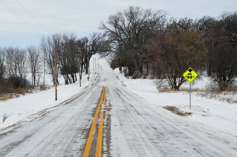 有公共汽车站标志的积雪的乡下公路 库存图片